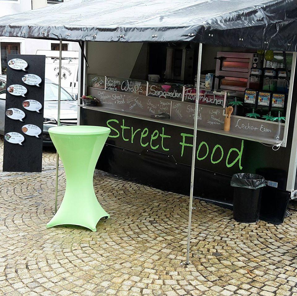Streetfood Truck auf Kopfsteinpflaster mit grünem Stehtisch